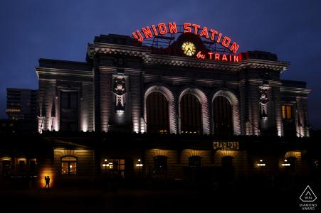Un couple se profile contre le bâtiment de la gare Union de Denver lors de leurs photos de fiançailles dans le bas du centre-ville