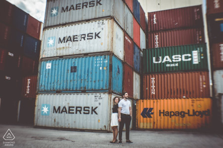 Stuttgart port engagement portrait with a background of stacked up shipping containers