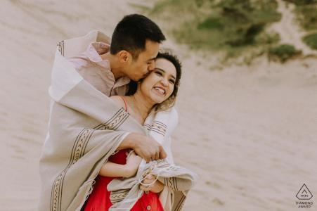 Una pareja riendo en la playa envuelto en una manta durante una sesión de retrato de compromiso en Cape Kiwanda, Oregon