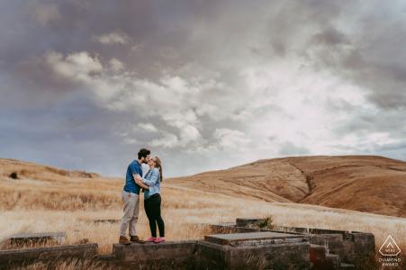 Godley Head, Christchurch NZ Couple s'embrassant sous les nuages dans un champ ouvert