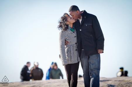 portraits de fiançailles avec un couple s'embrassant au sommet de Stone Mountain