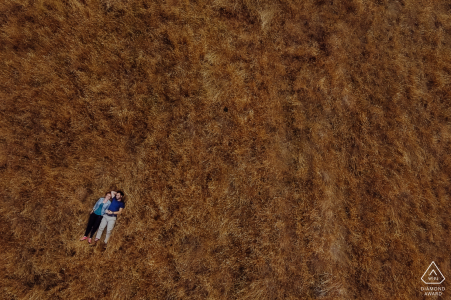 Godley Head, Christchurch NZ engagement drone portrait of a Couple lying in the grass