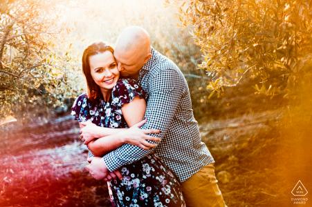Une photo vibrante et ensoleillée du couple heureux dans un vignoble d'oliviers alors que le soleil se couche derrière eux à la ferme Hillcrest