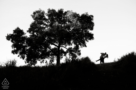 an Edmonton, Alberta Couple dips under tree during their black and white engagement photoshoot