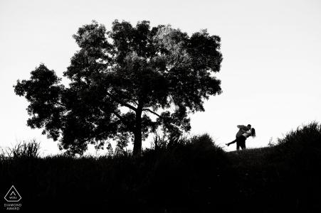 Un couple d'Edmonton, en Alberta, plonge sous un arbre pendant leur séance photo de fiançailles en noir et blanc