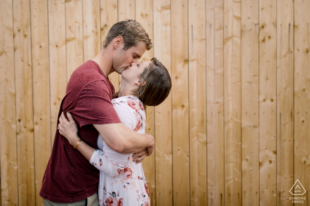 Couple in Lyon for their engagement shoot by a wooden wall/fence