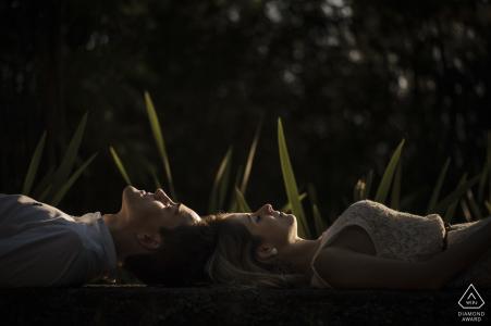 Paar liegt auf dem Rücken und schaut während eines Verlobungsshootings im Parque das Ruínas, Santa Teresa, Rio de Janeiro, Brasilien auf