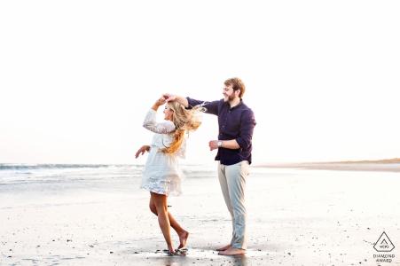 Session d'engagement à la plage à Avalon, New Jersey avec un couple qui tourne et danse au bord de l'eau à la plage