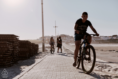 Bride and groom were kissing on the way, when two kids pass by on their bikes at Baleal Beach, Peniche, Portugal