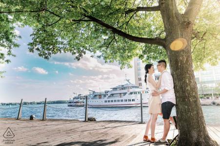 Verlobungsporträt des Paares Toronto, Ontario unter einem Baum an einem Hafen mit Booten