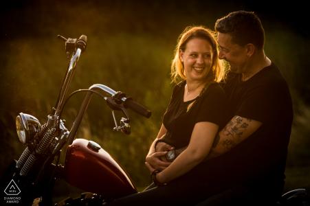Séance de portrait d'engagement Bovensluis Willemstad avec une moto Harley Davidson dans un joli coucher de soleil et un couple amoureux.