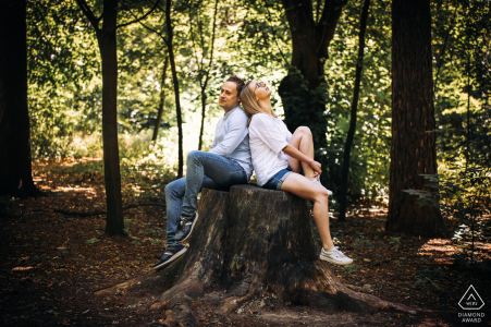 Young lovers sitting on a felled tree trunk at Mickiewicz Park, Lodz, Poland