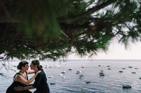Positano couple pose for a portrait during their engagement session by the waters edge in Italy
