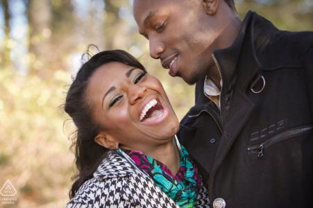 Les fiancés de Stone Mountain Park rient ensemble pendant les portraits de fiançailles