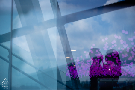 Singapore engaged couple posing for portraits with glass reflections and purple flowers