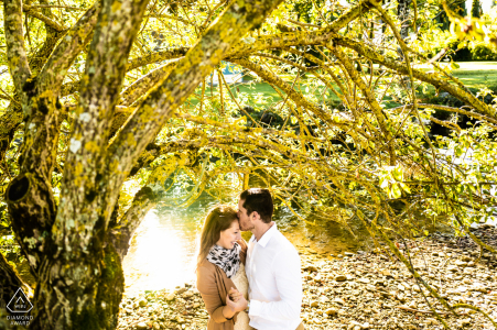Annecy lake - France couple kissing under a tree at the edge of a river