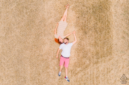 Vendée, France Couple lying in their freshly cut wheat field in th french courtyside, from above via drone