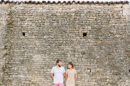 Vendée, Francia Pareja amorosa riendo y apoyado contra una pared en la campiña francesa