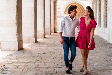 Una pareja de Venecia, Italia, caminan juntos sobre las piedras durante su sesión de retratos previa a la boda
