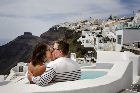 santorini, greece engagement shooting with a couple kissing high above the rest of the world