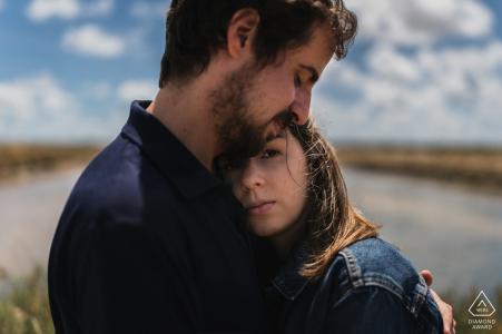 Noirmoutiers, France couple hugging under the clouds for an engagement portrait