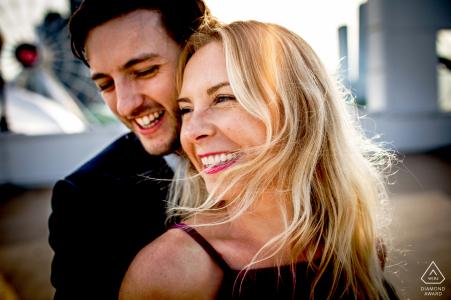 Un couple rit dans un rayon de soleil pendant leur portrait de fiançailles au Navy Pier Chicago, IL