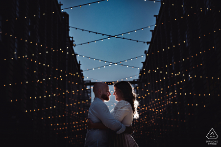 Industry city, Brooklyn couple Kiss portrait during engagement shoot under strings of lights