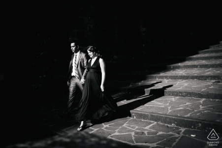 Sunlit engagement photos at Piazzale Michelangelo of the couple coming down the stairs in Florence