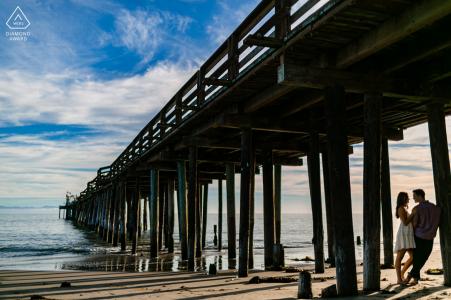 Fotos de compromiso de pareja amorosa del océano debajo del muelle en Capitola Beach, California