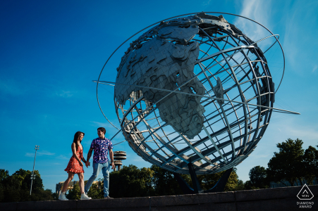 Fotografía de compromiso de la feria mundial de Nueva York de la pareja caminando por el unisphere en Flushing Meadows Corona Park