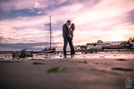 Barcos en el océano pareja de retratos de compromiso de un beso en la playa de CAP FERRET - FRANCIA