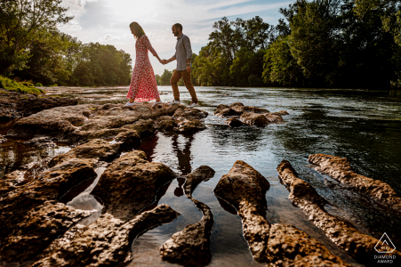 A couple crossing a river in Occitanie, France during an engagement portrait session