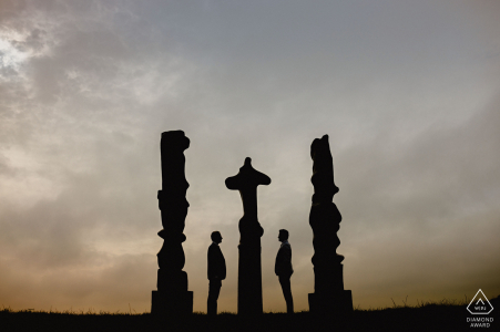 E-session of couple silhouetted with totem poles at the Yorkshire Sculpture Park
