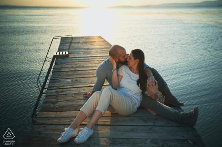 Retratos de pareja del lago Trasimeno con los dos solos en el muelle de madera al atardecer junto al agua
