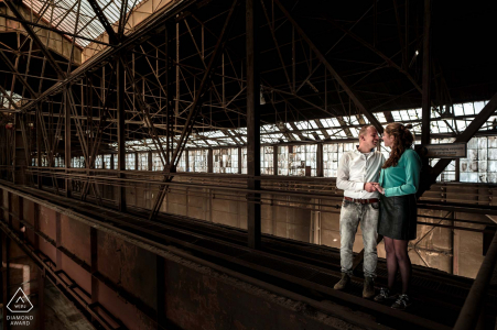The engaged couple are standing in the top of the building on a dangerous part of the roof for this engagement portrait at the Old steel factory in Alblasserdam