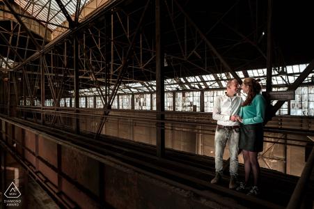 Les fiancés sont debout dans le haut du bâtiment sur une partie dangereuse du toit pour ce portrait de fiançailles à l'ancienne usine sidérurgique d'Alblasserdam.