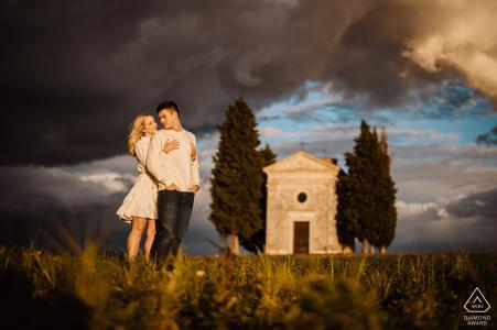 E-shoot d'un couple debout au coucher du soleil avec la chapelle de Vitaleta sur leur arrière-plan