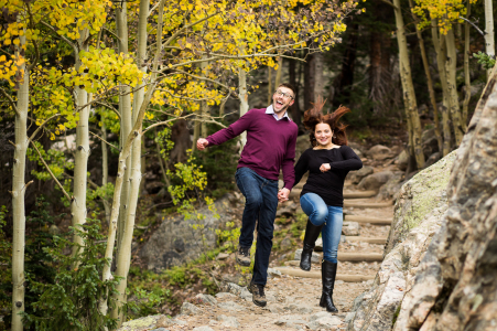 A Rocky Mountain National Park, Estes Park, Colorado couple take frolicking seriously as they skip down a hiking trail for their engagement portraits