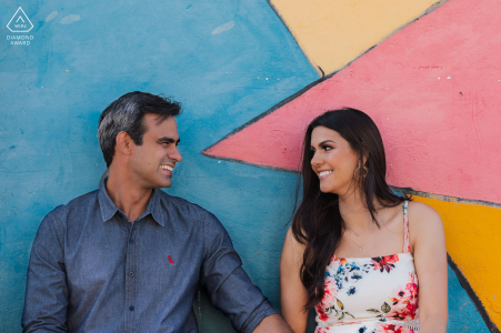 A Lavras Novas, Brazil Couple leaning against the colorful wall for their pre-wedding images