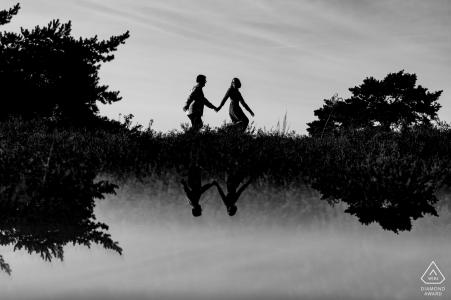 Brunssummerheide, Limbourg, Pays-Bas Couple avec la jeune fille ouvrant la voie en silhouette et réflexion lors de la séance de portrait d'engagement