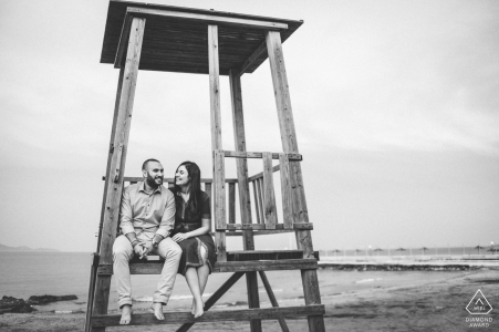 Athens, Greece couple sitting on beach lifeguard tower laughing in this black and white engagement photo