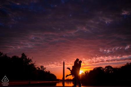 Der zukünftige Bräutigam hebt seinen Verlobten während eines herrlichen Sonnenaufgangs in Washington DC vor das Washington Monument