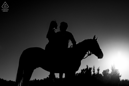 Silhouette portrait of couple on a horse and kissing in Cappadocia