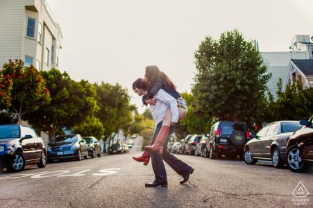 Photographie d'avant mariage à San Francisco d'un couple traversant la rue - Tu n'es pas lourd, tu es mon amour!