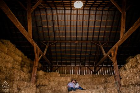 Une session de portrait de l'engagement d'automne dans une ferme du Maryland du couple assis sur des balles de foin empilées dans une grange