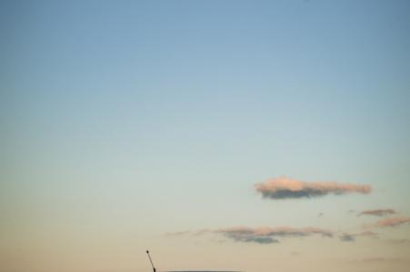 Eastern Shore Engagement Fotografie eines Paares, das auf einem Boot im Wasser mit Wolken über ihm sitzt
