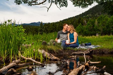 CO-fotosessie vóór de bruiloft met geëngageerde geliefden in het Rocky Mountain National Park, waar een stel te zien is dat samen van koffie geniet in RMNP