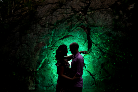 CO pre-wedding photo session with an engaged couple at Lair O the Bear park, Idledale, silhouetted in front of color-gelled rock face