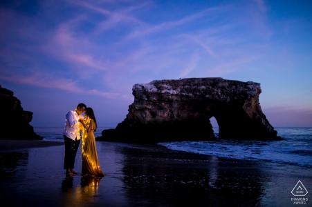 Fotografía previa a la boda y el compromiso de Santa Cruz en los puentes naturales de California después del atardecer iluminado con luces