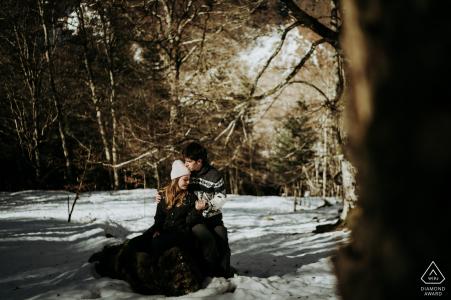 Séance photo de fiançailles et pré-mariage FR dans les Pyrénées France avec un couple sur un coffre dans la neige